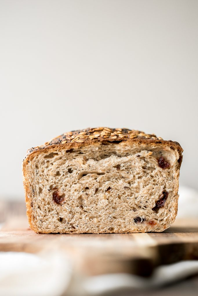 Whole wheat cranberry bread is chewy, fluffy and airy, packed with dried cranberries and seeds, and has a perfect crunchy crust topped with oats and seeds. | aheadofthyme.com