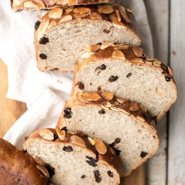 Sweet cinnamon raisin challah bread is airy, soft and fluffy with a beautiful golden crust coated with almonds. It is braided and baked in a loaf pan. | aheadofthyme.com