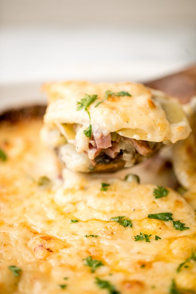 Easy creamy ham and potatoes au gratin is a great way to use leftover ham with tender sliced potatoes and a cheesy béchamel sauce. The best comfort food. | aheadofthyme.com