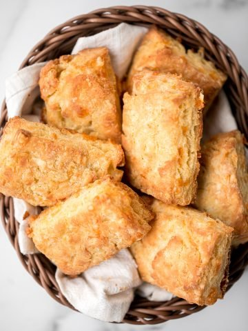 Flaky cornmeal cheddar biscuits are simple, buttery, cheesy, and so delicious. These savoury biscuits with perfect golden tops are quick and easy to make. | aheadofthyme.com