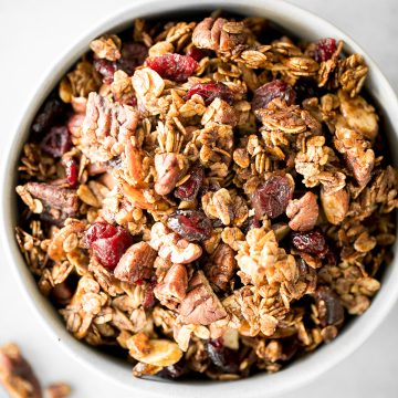Quick and easy gingerbread granola with nuts, cranberries and warm winter spices is vegan, gluten-free, and refined sugar-free. The best Christmas snack. | aheadofthyme.com
