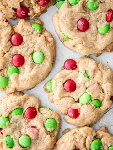 Festive red and green M&M Christmas cookies are super soft and chewy with the crispiest edges. Quick and easy to make in 20 minutes with no chill time.   aheadofthyme.com
