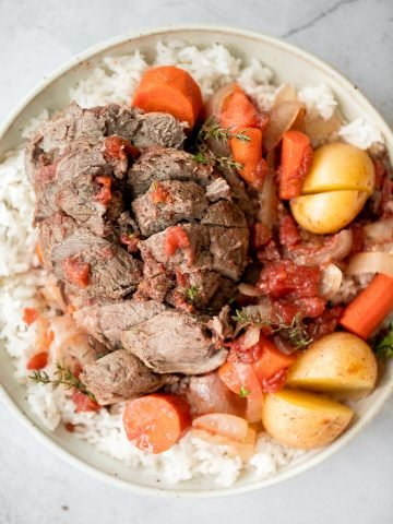 Easy Mediterranean slow cooker leg of lamb with vegetables is succulent, tender, juicy, and flavourful, seasoned with fresh herbs. Prep the crockpot in just 15 minutes.   aheadofthyme.com