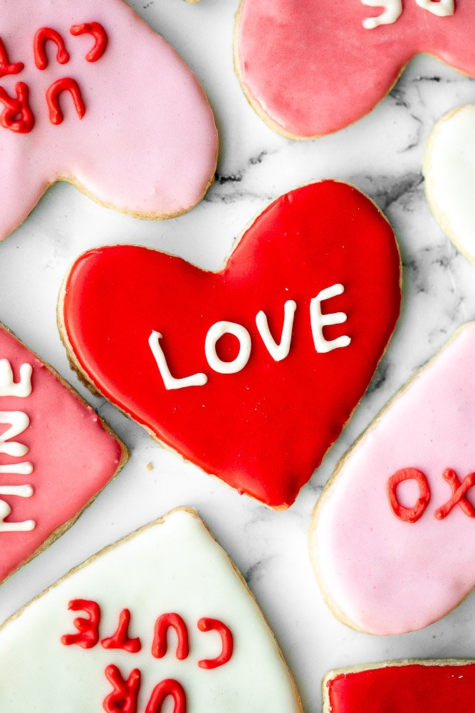 Valentine's Day heart sugar cookies are crisp on the outside, soft inside, and made festive with red and pink royal icing decorated on top. | aheadofthyme.com