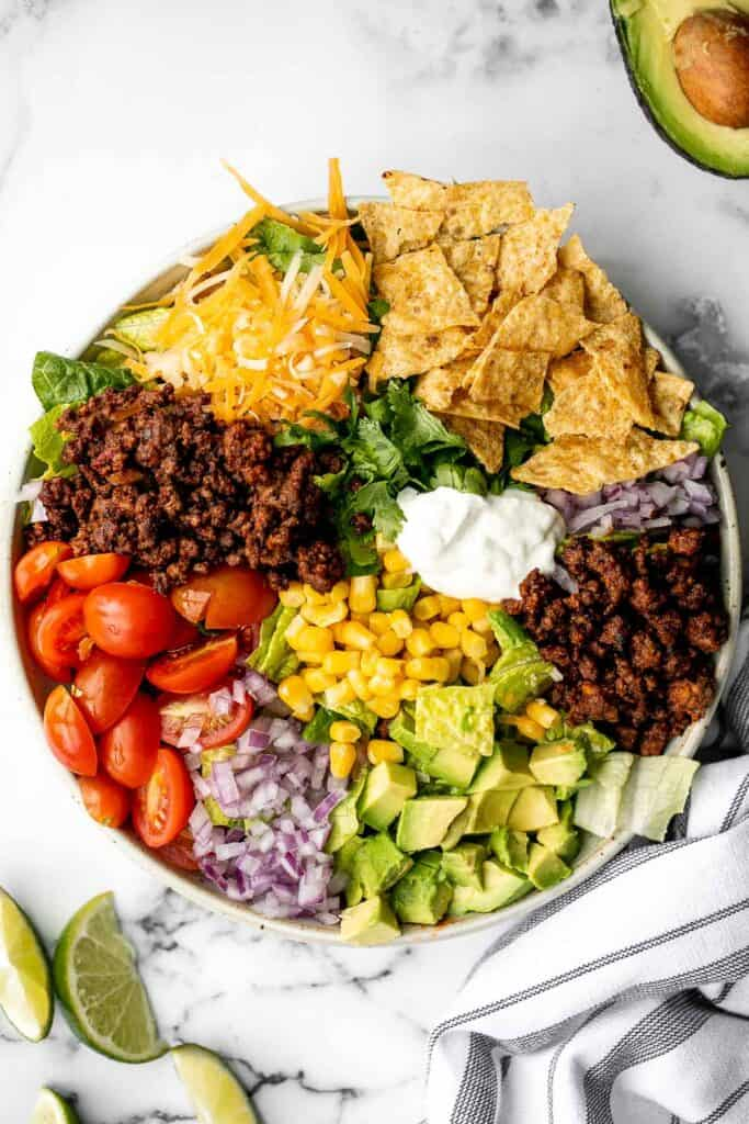 Beef taco salad is a simple, filling, and delicious meal loaded with your favorite taco fillings, and a creamy lime dressing. Make it in 20 minutes. | aheadofthyme.com