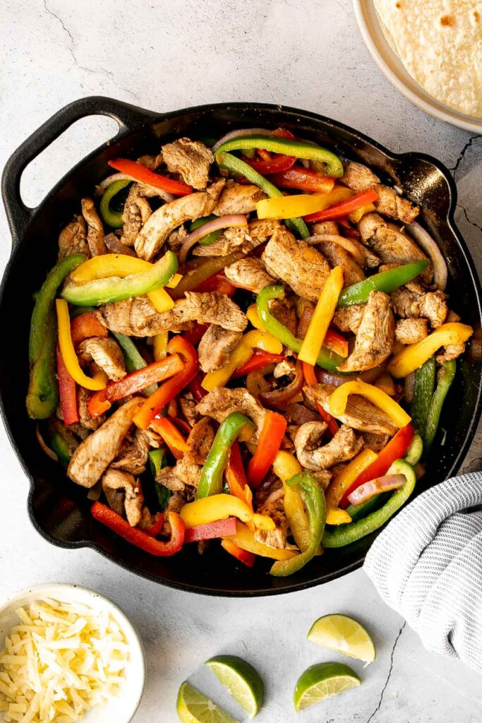 Skillet chicken fajitas are a light, fresh, and sizzling dish bursting with flavour, packed with colorful vegetables, and wrapped in warm tortillas. | aheadofthyme.com