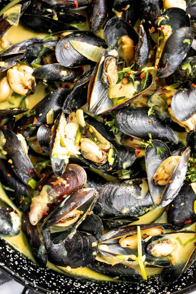 Yellow curry mussels are the epitome of delicious seafood - creamy, spicy, and savory. This flavourful one pot dish is quick + easy to make in 25 minutes. | aheadofthyme.com