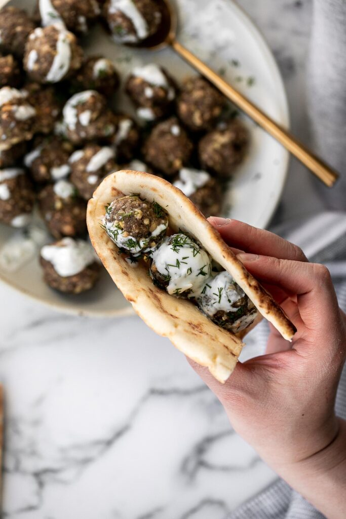 Baked Greek meatballs are juicy, tender, flavorful, and delicious. They are quick and easy to make in 30 minutes, and freezer-friendly. Serve with tzatziki.   aheadofthyme.com