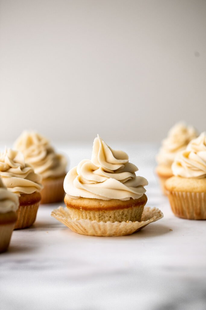 Moist vanilla cupcakes with buttercream frosting are soft, fluffy, simple, sweet, and delicious. Secret ingredient yogurt keeps them moist for days! | aheadofthyme.com