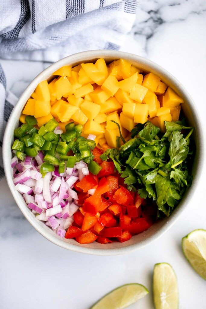 Fresh mango salsa is sweet, tangy, and delicious. It's a quick and easy recipe that you can whip up with just 6 ingredients and in under 10 minutes.   aheadofthyme.com