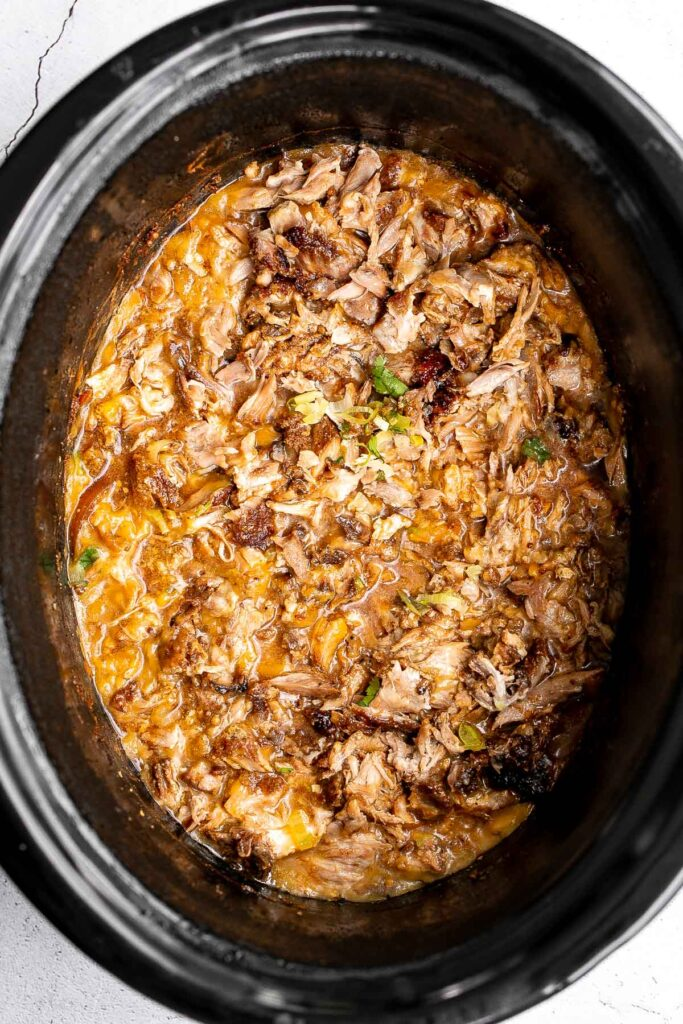 Crispy, shredded slow cooker carnitas (pulled pork) are a Mexican favorite that you can make at home. Packed with flavor, easy to make, and minimal dishes. | aheadofthyme.com