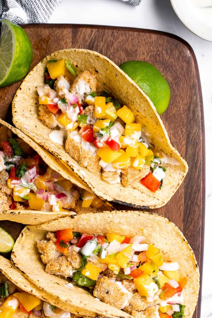 Fish stick tacos are fun, quick, easy, and delicious. Crispy breaded fish sticks are topped with a homemade mango salsa and a drizzle of lime crema. | aheadofthyme.com