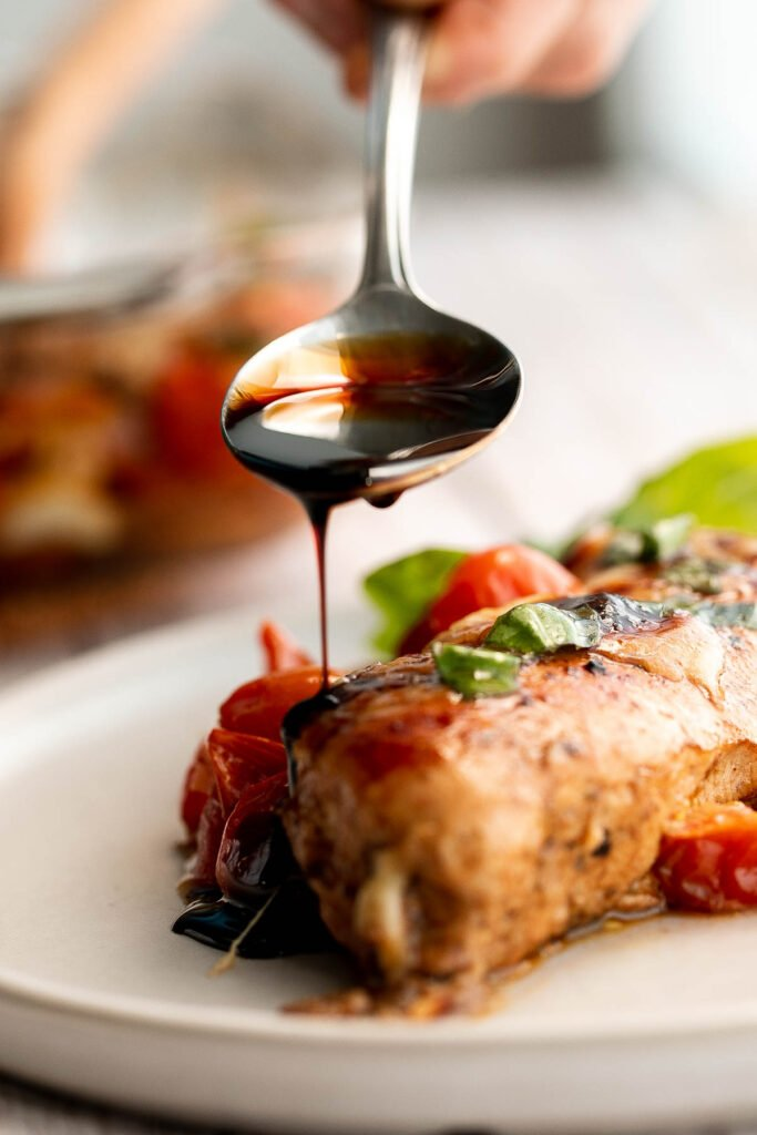 Baked caprese chicken is tender, juicy, and delicious, topped with burst tomatoes, mozzarella cheese, fresh basil, and a drizzle of balsamic glaze. | aheadofthyme.com