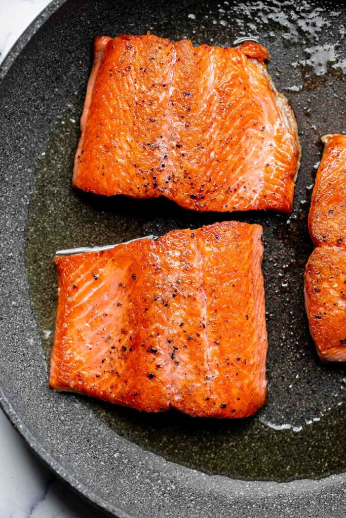 Creamy garlic salmon is a quick easy one-pan meal ready in under 30 minutes, with seared flaky tender salmon tossed in a delicious creamy garlic sauce. | aheadofthyme.com