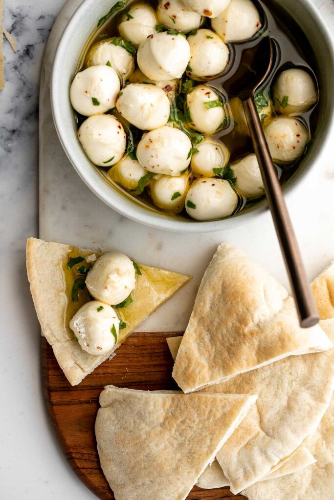 Marinated mozzarella balls is a delicious and simple yet stunning appetizer, made with fresh bocconcini soaked in olive oil, garlic, and fresh herbs.   aheadofthyme.com