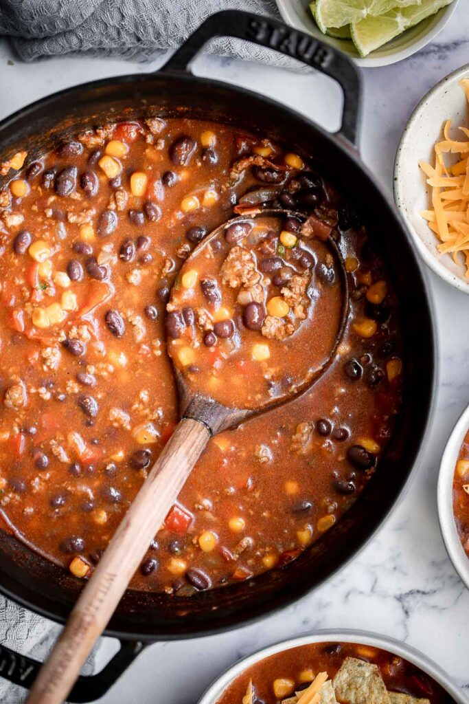 Beef taco soup is a delicious take on tacos, transforming it into a hearty, wholesome, filling soup topped with all the taco fixings. Ready in 30 minutes. | aheadofthyme.com